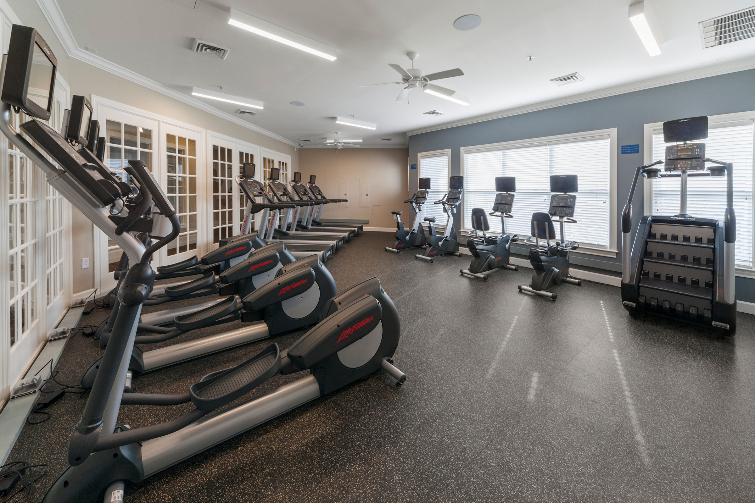 Bright fitness center with treadmills, fitness bikes and stair stepper.