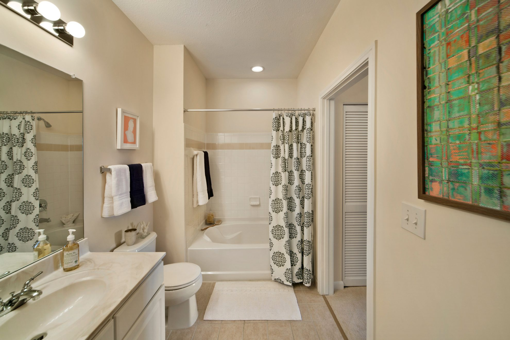 A master bathroom with a large mirror and tiled bathroom.